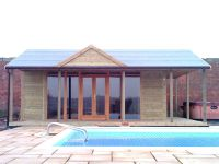 Pavilion used for swimming pool changing room with full length glass doors and windows. Additional gable to front of roof