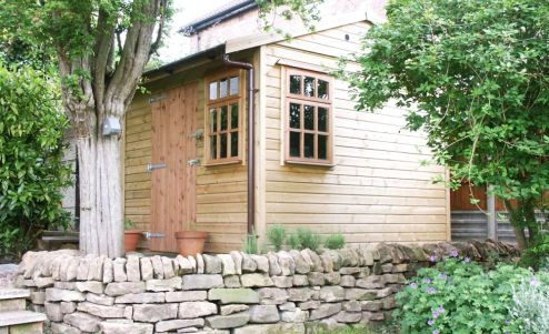 A sturdy Warwick Buildings Garden Storage Building fitting neatly into the available space. Customer choice here includes Georgian Style Windows.